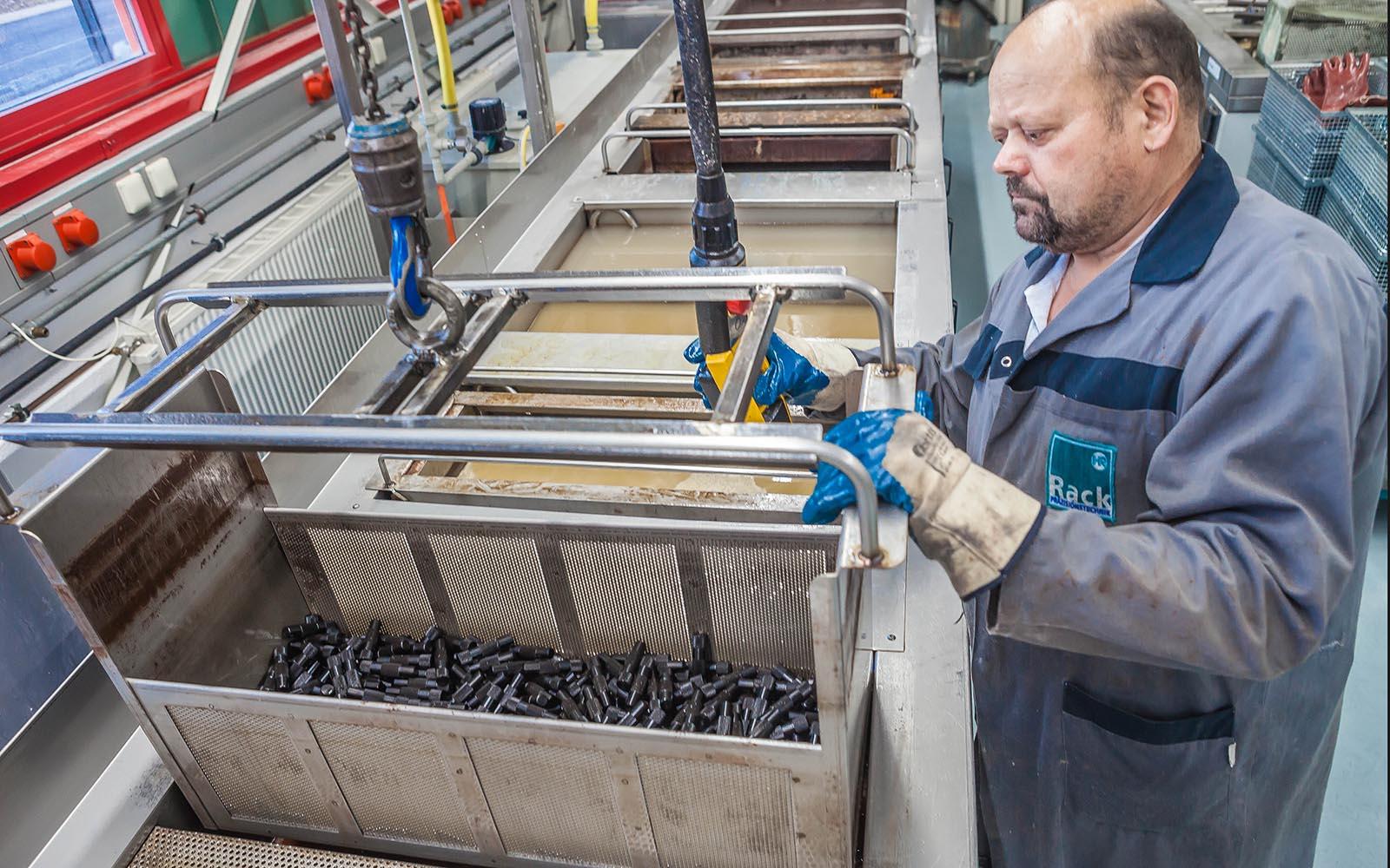 Bünieren, Mitarbeiter an Brünierstrasse, hebt Korb mit Teilen heraus
