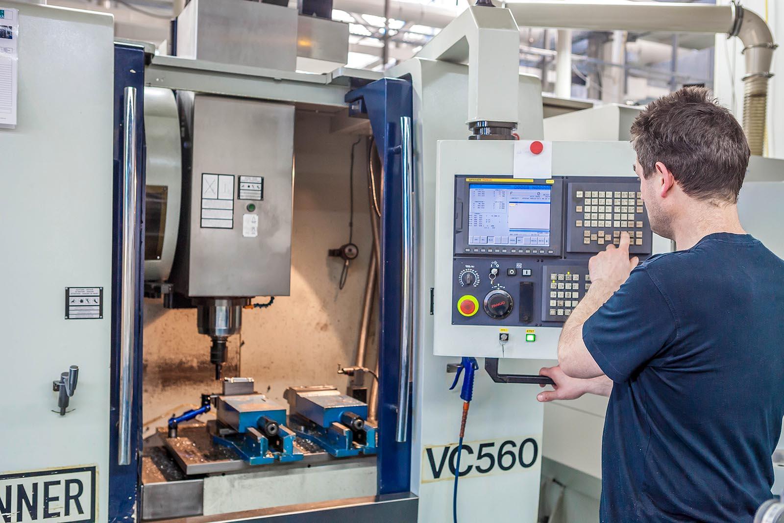 Arbeiter an CNC-Maschine, nimmt Einstellungen vor VC560
